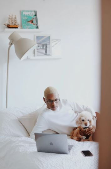 Man on bed with his dog and laptop working from home